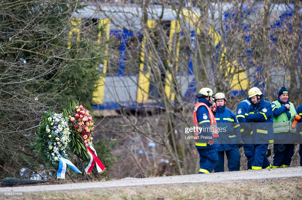 Rescue workers stand in front of two chaplets near the wreckage of two trains that collided head-on the day before in Bavaria on February 10, 2016 near Bad Aibling, Germany. Authorities say at least nine people are dead and over 100 injured in the collision between two trains of the Meridian local commuter train service that occurred at approximately 7:00 am yesterday.
