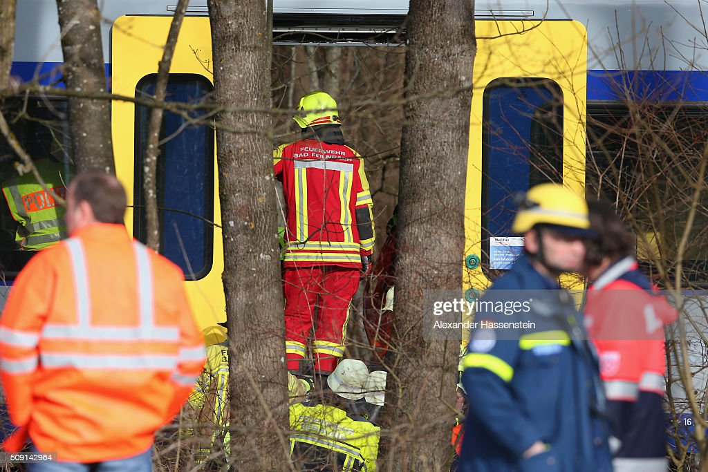 Rescue workers stand near the wreckage of two trains that collided head-on several hours before in Bavaria on February 9, 2016 near Bad Aibling, Germany. Authorities say at least four people are dead and over 150 injured in the collision between two trains of the Meridian local commuter train service that occurred at approximately 7 am.
