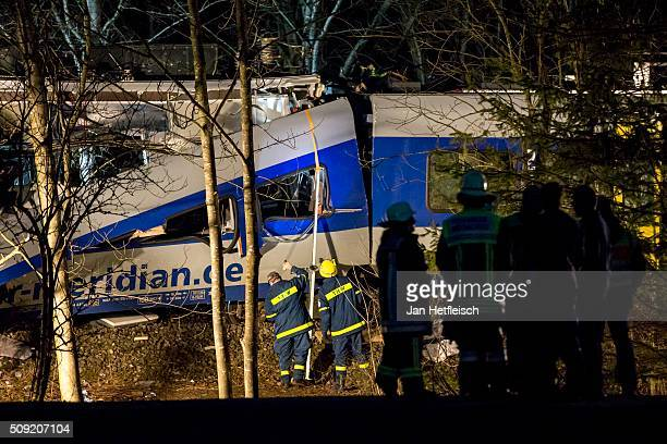 Rescue workers stand near the wreckage of two trains that collided headon several hours before in Bavaria on February 9 2016 near Bad Aibling Germany...