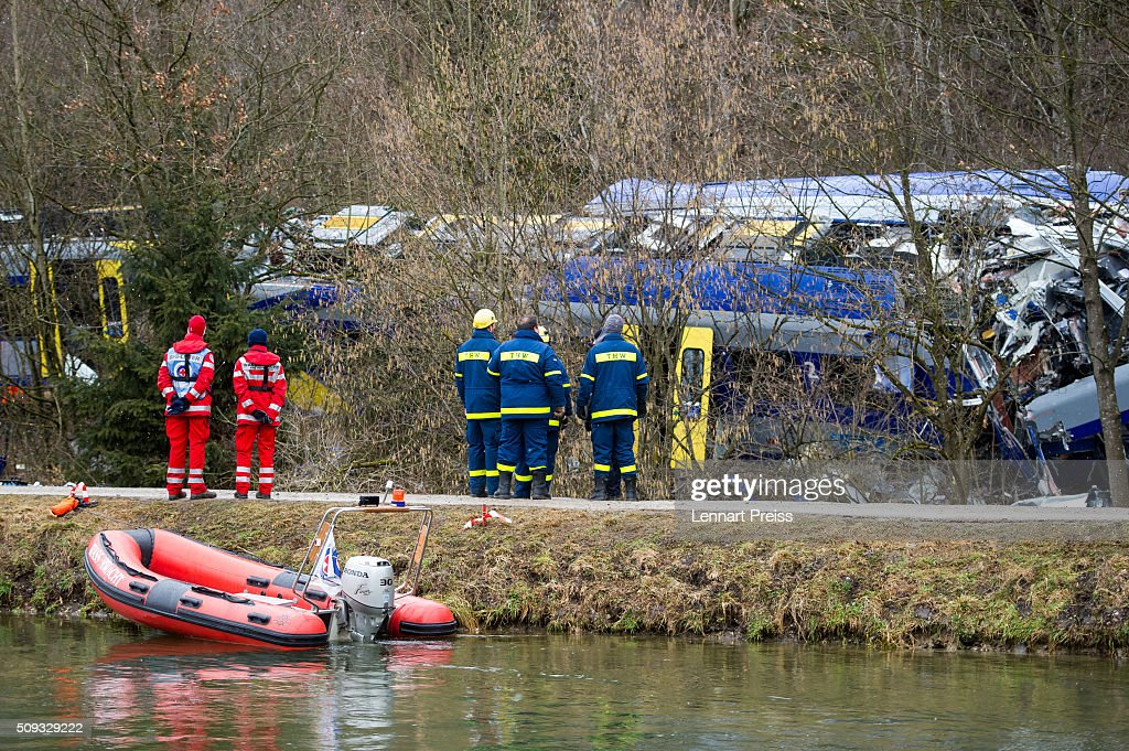 Rescue workers stand near the wreckage of two trains that collided head-on the day before in Bavaria on February 10, 2016 near Bad Aibling, Germany. Authorities say at least nine people are dead and over 100 injured in the collision between two trains of the Meridian local commuter train service that occurred at approximately 7:00 am yesterday.