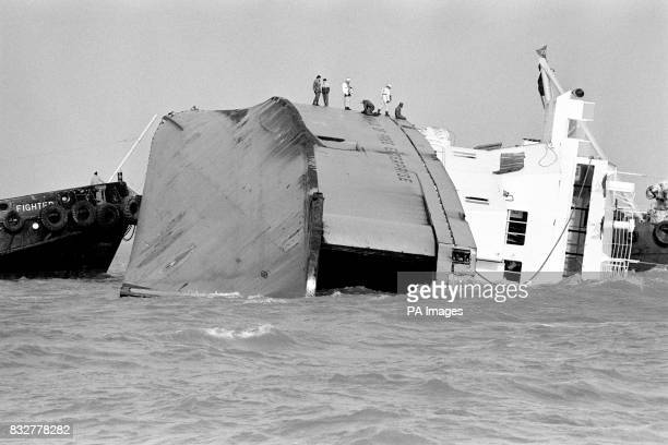 Rescue workers stand on the side of the halfsubmerged car ferry Herald of Free Enterprise which capsized of the Belgian port of Zeebrugge claiming...