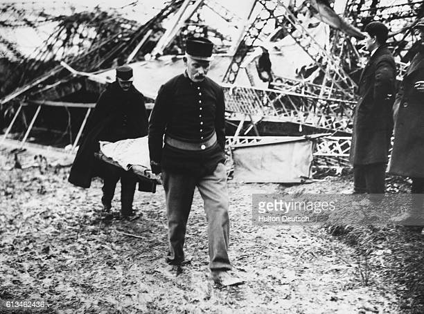 Rescue workers stretcher a body away from the wreckage of the R101 airship which crashed into a hillside during a rainstorm | Location Near Beauvais...