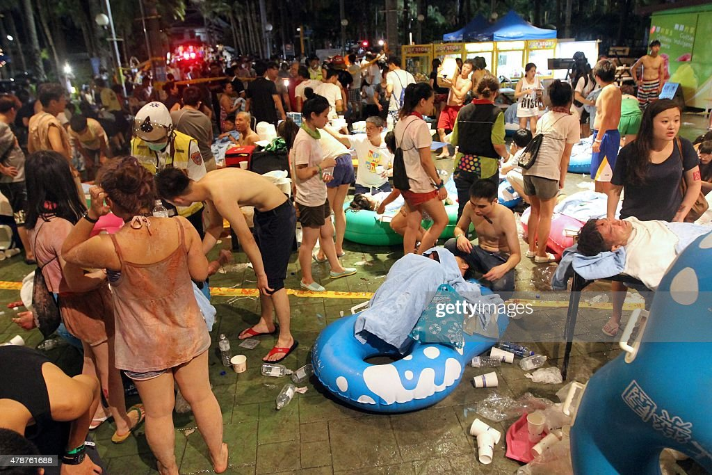 Rescue workers tend to injured people at the Formosa Fun Coast amusement park after an explosion in the Pali district of New Taipei City on June 27...