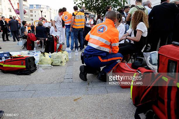 Rescue workers tend to victims at the site of a train accident on July 12 2013 at the railway station of BretignysurOrge near Paris At least six...
