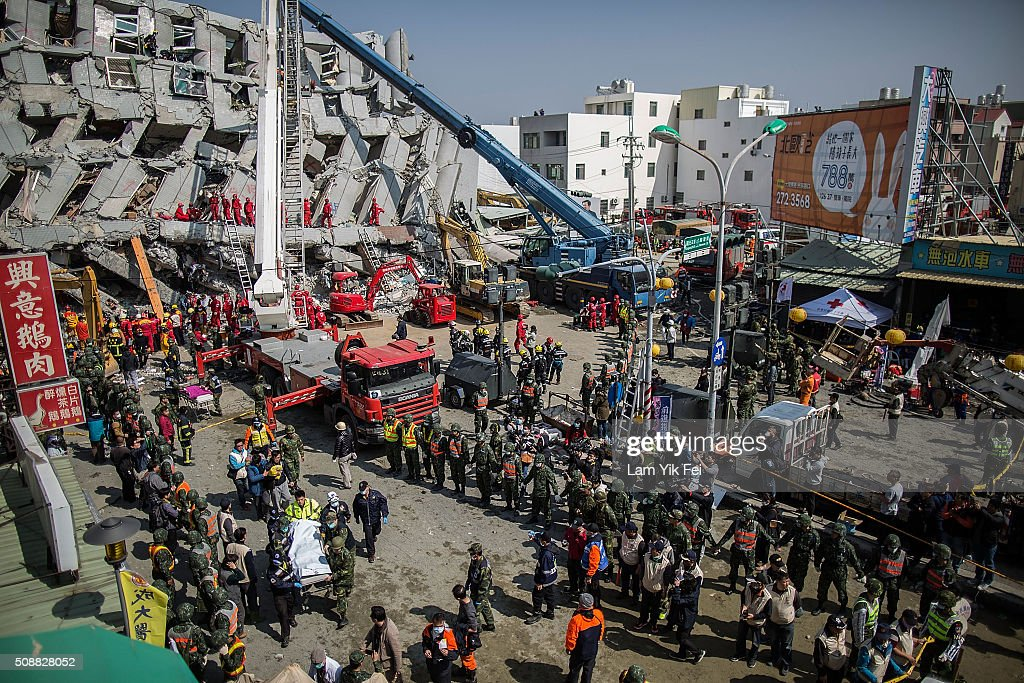 Rescue workers transport a body near a collapsed building on February 7, 2016 in Tainan, Taiwan. A magnitude 6.4 earthquake hit southern Taiwan early Saturday, toppling several buildings, killing at least fourteen people, and leaving over one hundred missing in Tainan.