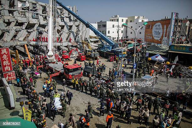 Rescue workers transport a body near a collapsed building on February 7 2016 in Tainan Taiwan A magnitude 64 earthquake hit southern Taiwan early...