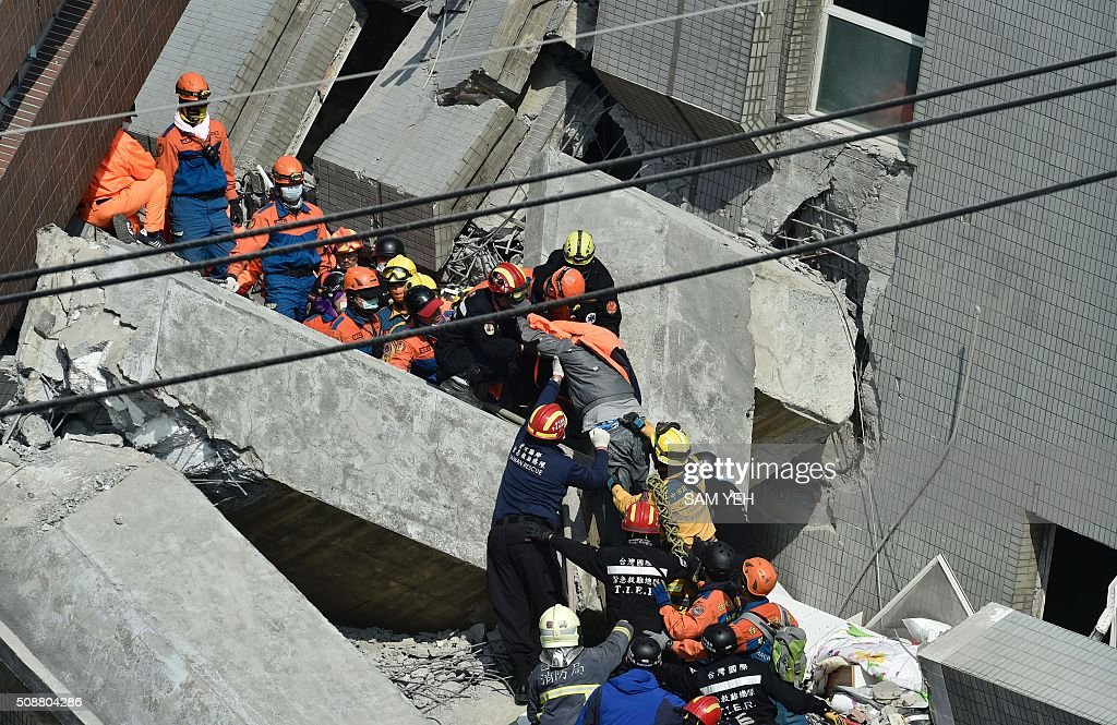 Rescue workers transport a survivor (C-in grey top, under orange jacket) found in the rubble at the Wei-kuan apartment complex on the second day of rescue operations following a 6.4 magnitude earthquake in southern Taiwan's city of Tainan on February 7, 2016. Rescuers searched through the night hoping to free residents trapped in buildings toppled by the deadly earthquake in Taiwan, as survivors recalled being plucked to safety from their ruined homes. AFP PHOTO / Sam Yeh / AFP / SAM YEH