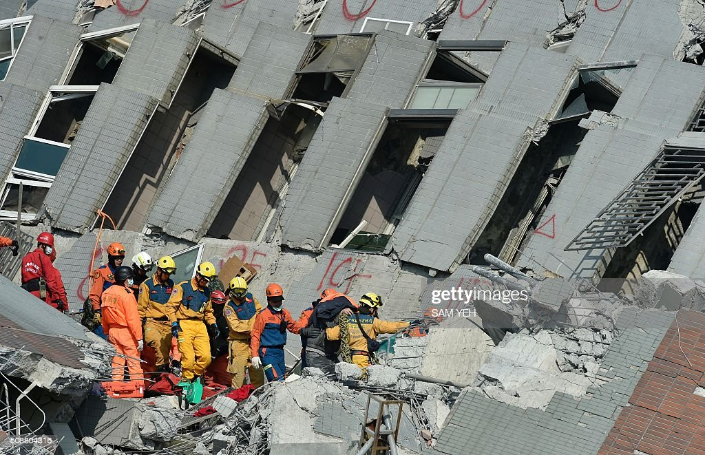 Rescue workers transport a survivor (3rd R) found in the rubble at the Wei-kuan apartment complex on the second day of rescue operations following a 6.4 magnitude earthquake in southern Taiwan's city of Tainan on February 7, 2016. Rescuers searched through the night hoping to free residents trapped in buildings toppled by the deadly earthquake in Taiwan, as survivors recalled being plucked to safety from their ruined homes. AFP PHOTO / Sam Yeh / AFP / SAM YEH