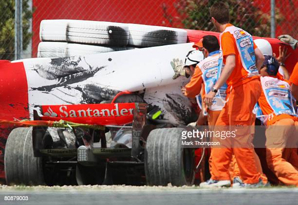 Rescue workers try to retrieve the crashed car of Heikki Kovalainen of Finland and McLaren Mercedes as he sits imbedded in the safety barriers after...