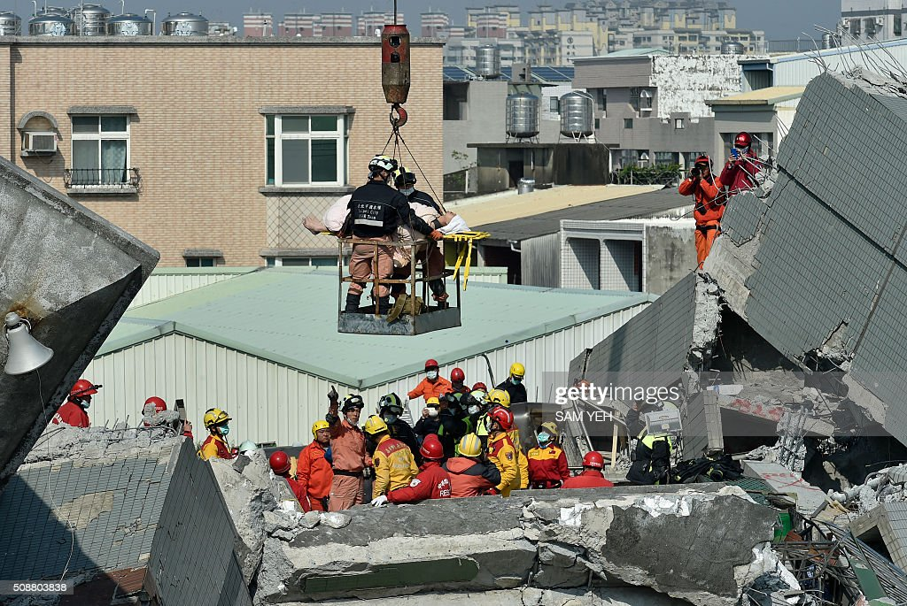 Rescue workers use a crane to transport a survivor (C) found in the rubble at the Wei-kuan apartment complex on the second day of rescue operations following a 6.4 magnitude earthquake in southern Taiwan's city of Tainan on February 7, 2016. Rescuers searched through the night hoping to free residents trapped in buildings toppled by the deadly earthquake in Taiwan, as survivors recalled being plucked to safety from their ruined homes. AFP PHOTO / Sam Yeh / AFP / SAM YEH