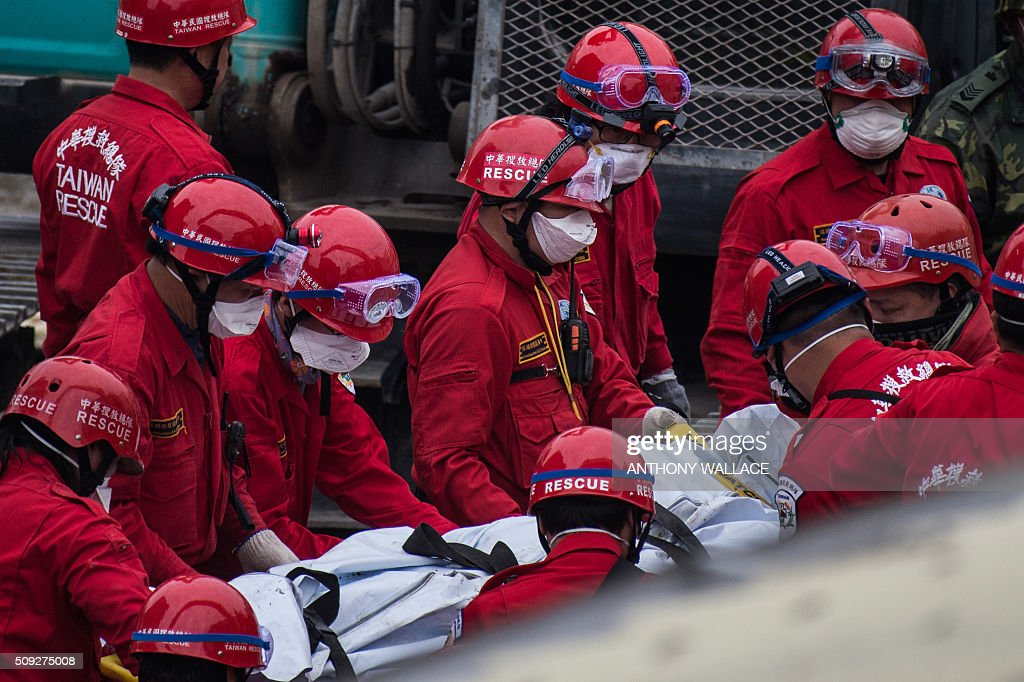 Rescue workers use a stretcher to carry the body of a male student, who was thought to be alive but died before being rescued from the remains of the Wei-Kuan complex which collapsed in the 6.4 magnitude earthquake, in the southern Taiwanese city of Tainan on February 10, 2016. The developer of a Taiwan apartment complex that collapsed during a strong earthquake was arrested February 9, as rescuers reported hearing signs of life in the rubble where some 100 people are still trapped. AFP PHOTO / ANTHONY WALLACE / AFP / ANTHONY WALLACE