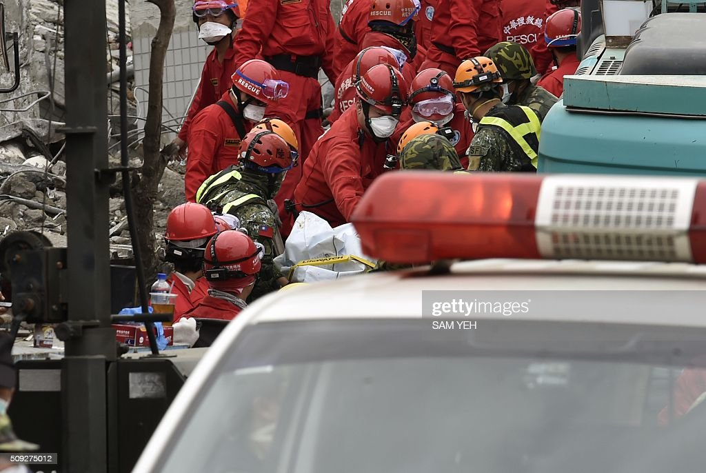 Rescue workers use a stretcher to carry the body of a male student, who was thought to be alive but died before being rescued from the remains of the Wei-Kuan complex which collapsed in the 6.4 magnitude earthquake, in the southern Taiwanese city of Tainan on February 10, 2016. The developer of a Taiwan apartment complex that collapsed during a strong earthquake was arrested February 9, as rescuers reported hearing signs of life in the rubble where some 100 people are still trapped. AFP PHOTO / Sam Yeh / AFP / SAM YEH