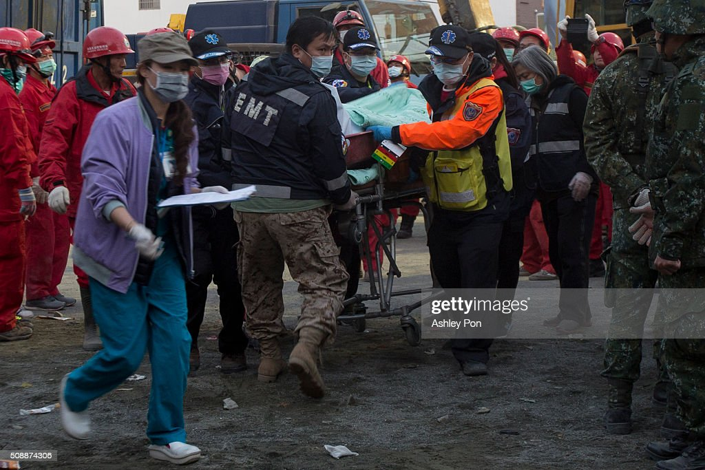 Rescue workers use a stretcher to take a victim to an ambulance at the site of collapsed buildings on February 7, 2016 in Tainan, Taiwan. A magnitude 6.4 earthquake hit southern Taiwan early Saturday, toppling several buildings, killing at least fourteen people, and leaving over one hundred missing in Tainan.