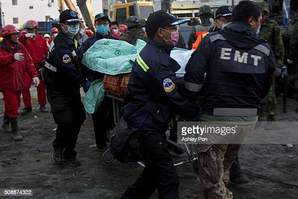 Rescue workers use a stretcher to take a victim to an ambulance at the site of collapsed buildings on February 7 2016 in Tainan Taiwan A magnitude 64...