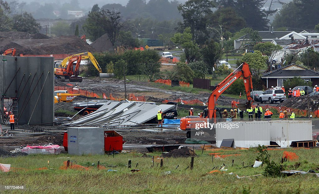 Rescue workers use heavy machinery amongst debris at the site where two people were killed in Hobsonville, Auckland on December 6, 2012 after packed wind gusts of up to 110 kilometres (70 miles) per hour, struck suburban Hobsonville in the afternoon. A freak storm described by police as a tornado hit New Zealand's largest city Auckland on December 6 causing 'utter devastation', with three people reportedly killed in ferocious winds. AFP PHOTO / Michael Bradley