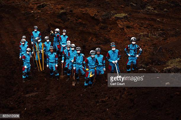 Rescue workers wait to be called upon as a digger moves earth from the area where houses were destroyed by a landslide following an earthquake on...