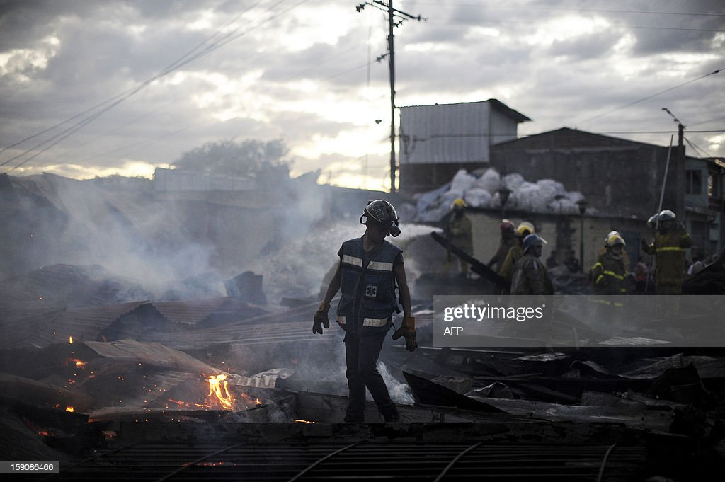 Rescue workers walk amid smouldering rubble following a blaze that destroyed the San Esteban Church, an historical landmark in downtown San Salvador, El Salvador on January 7, 2012. The San Esteban was built in the 19th century in Belgium, transported and assembled in one of the oldest localities of the capital city. AFP PHOTO/ Jose CABEZAS