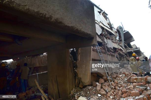 Rescue workers walk on the site of a collapsed building under construction in Canacona about 80 kms from the capital Panaji of western Goa state on...