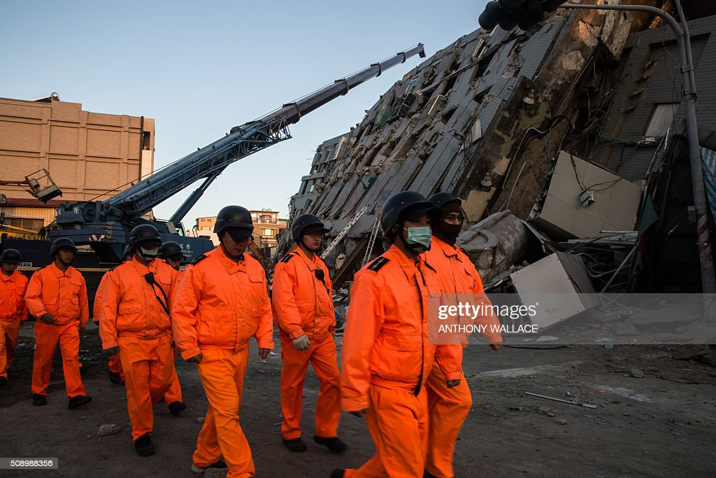 Rescue workers walk past the remains of a building which collapsed in the 6.4 magnitude earthquake, in the southern Taiwanese city of Tainan on February 8, 2016. Rescuers raced on February 7 to free around 120 people buried under the rubble of an apartment complex felled by an earthquake in southern Taiwan that left 34 confirmed dead, as an investigation began into the collapse. AFP PHOTO / ANTHONY WALLACE / AFP / ANTHONY WALLACE