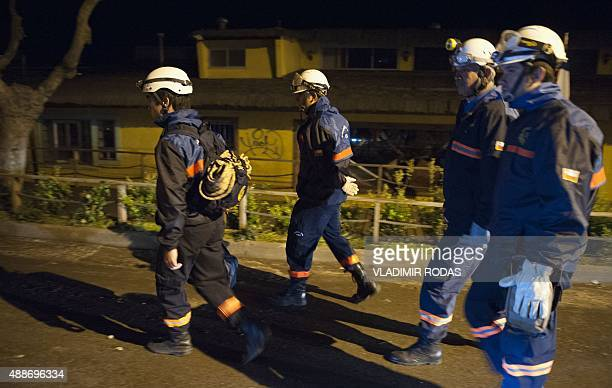 Rescue workers walk through the streets after a large earthquake in Concon some 110 kms northwest of Santiago on September 16 2015 The 83magnitude...