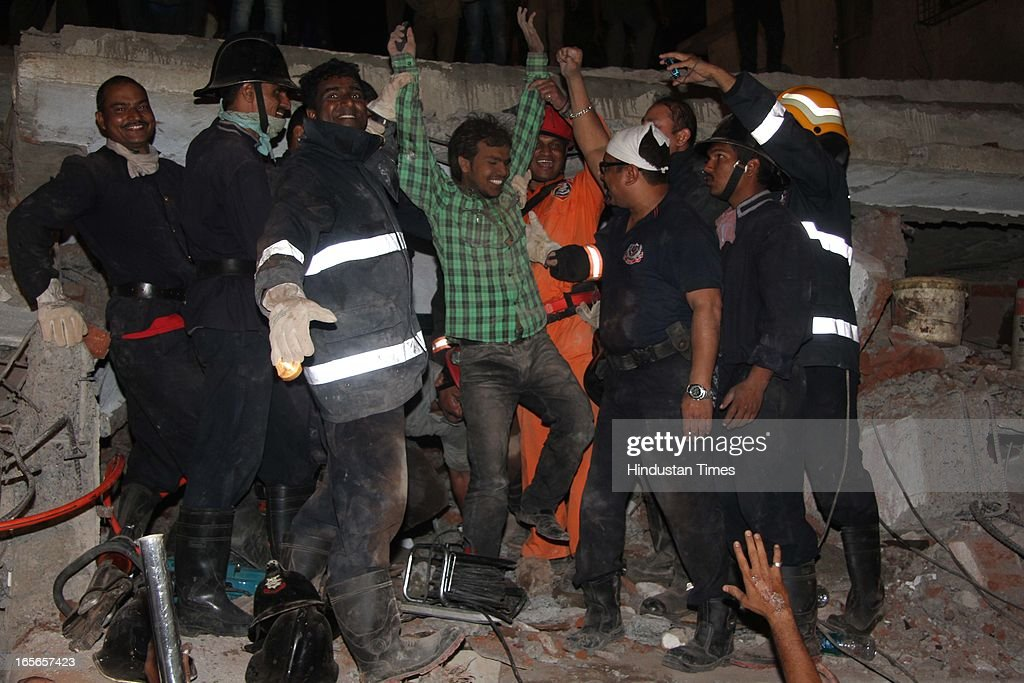 Rescue workers with survivor the building collapse at Lucky compound on April 4, 2013 in Thane, India. The death toll has risen to 39 while at least 69 people are injured. The building is illegal and constructed on Forest land. Police have registered a case against builders Salil and Khalil Jamadar under Section 304.
