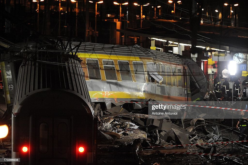 Rescue workers work alongside a derailed carriage after a train accident on July 12, 2013 in Bretigny-sur-Orge, France. An intercity train carrying 385 passengers, traveling from Paris towards Limoges, derailed crashing into a station platform leaving six people dead and a further 26 injured. on July 12, 2013 in Bretigny-sur-Orge, France.