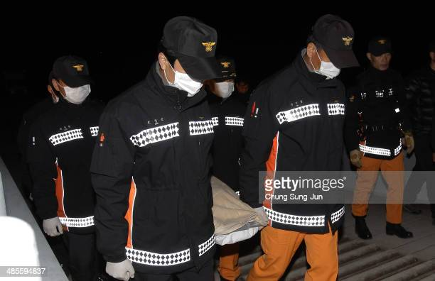 Rescue works carry a victim of the sunken ferry off the coast of Jindo Island on April 19 2014 in Jindogun South Korea At least twenty nine people...