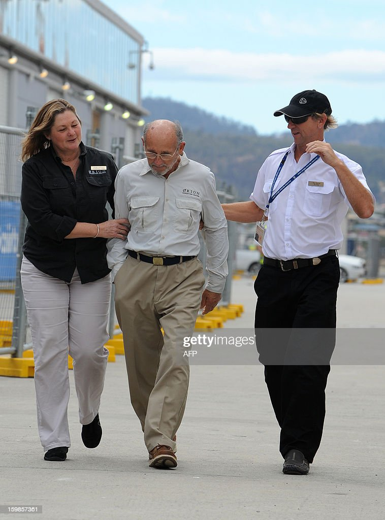 Rescued French sailor Alain Delord (C) walks with Antarctic expedition leader Margie McIntyre (L) and Zodiac rescue crewman Tim Sharpe (R), after stepping off the Antarctic cruise vessel the MV Orion at Macquarie dock, Hobart on January 22, 2013. A French sailor walked off the cruise ship that saved him after he spent three days adrift in a life-raft in the remote Southern Ocean, smiling and assisted by his rescuers. Alain Delord was marooned on a life-raft in mountainous seas about 500 nautical miles from southern Australia's Tasmania after his yacht was badly damaged in perilous weather during a solo round-the-world sailing attempt.