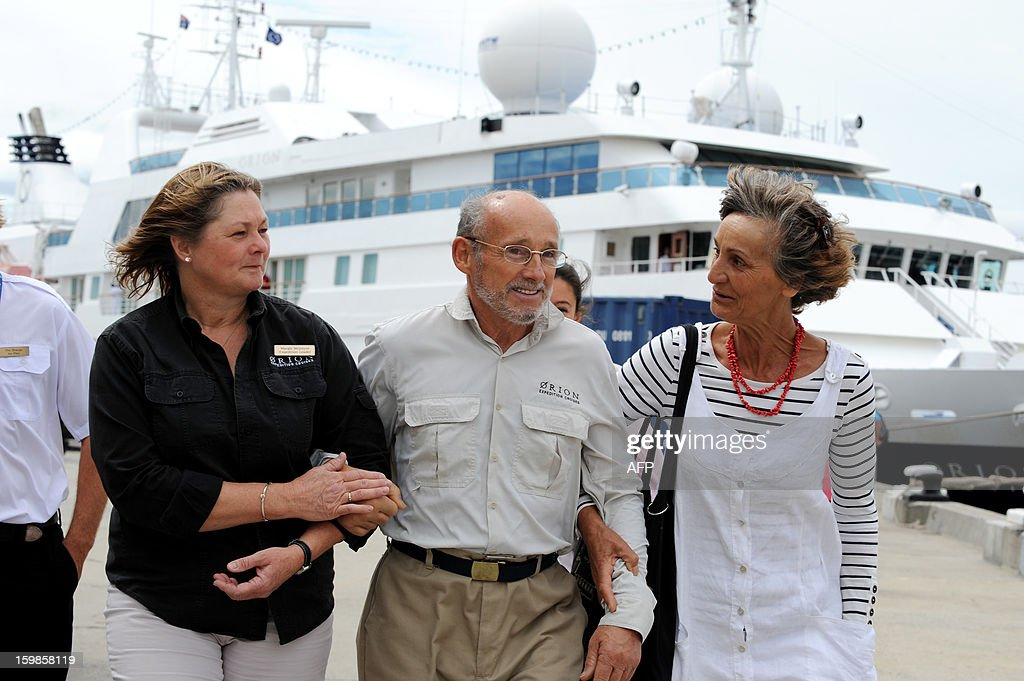 Rescued French sailor Alain Delord walks with Antarctic expedition leader Margie McIntyre (L) and Alliance Francaise representative Patricia Riley, takes his first steps on dry land, after stepping off the Antarctic cruise vessel the MV Orion, at Macquarie dock, in Hobart on January 22, 2013. A French sailor walked off the cruise ship that saved him after he spent three days adrift in a life-raft in the remote Southern Ocean, smiling and assisted by his rescuers. Alain Delord was marooned on a life-raft in mountainous seas about 500 nautical miles from southern Australia's Tasmania after his yacht was badly damaged in perilous weather during a solo round-the-world sailing attempt. AFP PHOTO / DAN HIMBRECHTS