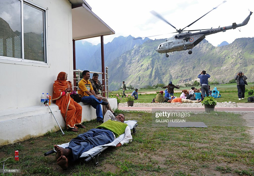 A rescued Hindu pilgrim lies on a stretcher while an Indian Air Force Mi-17 helicopter hovers in the background at the Joshimath helipad following flash floods in northern Uttarkhand state on June 29, 2013. More than 100,000 mainly pilgrims and tourists have been evacuated from the disaster zone while some 4,000 remain in relief camps after the flash floods and landslides that hit the state on June 15.