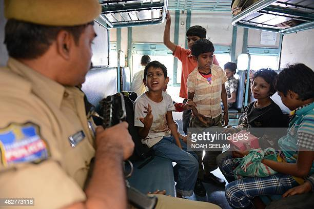 A rescued Indian child labourer gestures to a policeman while on board a Patnabound express train at a railway station in Secunderabad on February 5...