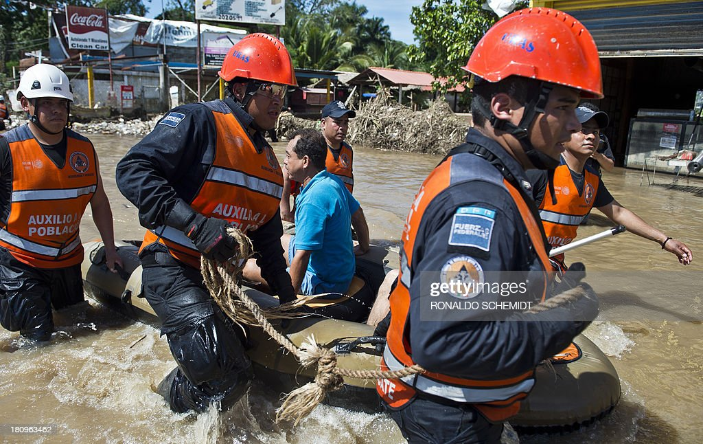 A rescued man is taken to safety by Mexican Federal Police officers on an inflatable dinghy in a flooded street of Acapulco, state of Guerrero, Mexico, on September 18, 2013 as heavy rains hit the country. Mexican authorities scrambled Tuesday to launch an air lift to evacuate tens of thousands of tourists stranded amid floods in the resort of Acapulco following a pair of deadly storms. The official death toll rose to 47 after the tropical storms, Ingrid and Manuel, swarmed large swaths of the country during a three-day holiday weekend, sparking landslides and causing rivers to overflow in several states.