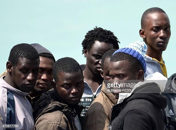 Rescued migrants wait before disembarking off the Italian Guardia Costiera vessel Fiorillo at the Sicilian harbour of Catania on April 24 2015...