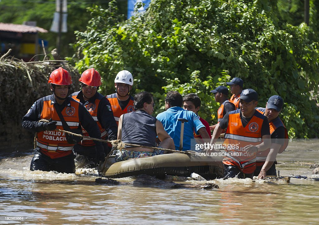 Rescued people are taken to safety by Mexican Federal Police officers on an inflatable dinghy in a flooded street of Acapulco, state of Guerrero, Mexico, on September 18, 2013 as heavy rains hit the country. Mexican authorities scrambled Tuesday to launch an air lift to evacuate tens of thousands of tourists stranded amid floods in the resort of Acapulco following a pair of deadly storms. The official death toll rose to 47 after the tropical storms, Ingrid and Manuel, swarmed large swaths of the country during a three-day holiday weekend, sparking landslides and causing rivers to overflow in several states.