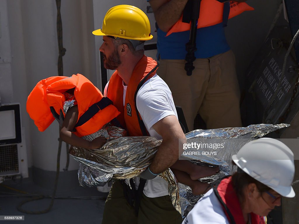 A rescuer holds a child during a rescue operation at sea with the Aquarius, a former North Atlantic fisheries protection ship now used by humanitarians SOS Mediterranee and Medecins Sans Frontieres (Doctors without Borders), on May 24, 2016 in the Mediterranean sea in front of the Libyan coast. / AFP / GABRIEL