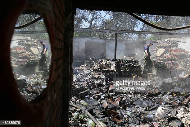 A rescuer is reflected in a mirror as he stands in a food storage unit destroyed as a result of shelling between Ukrainian forces and proRussian...