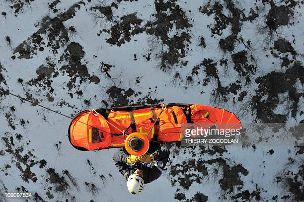 A rescuer of the gendarmerie mountain squad of Murat winches a fake injured person in safety during an exercice on February 11 2011 in Lavignerie...