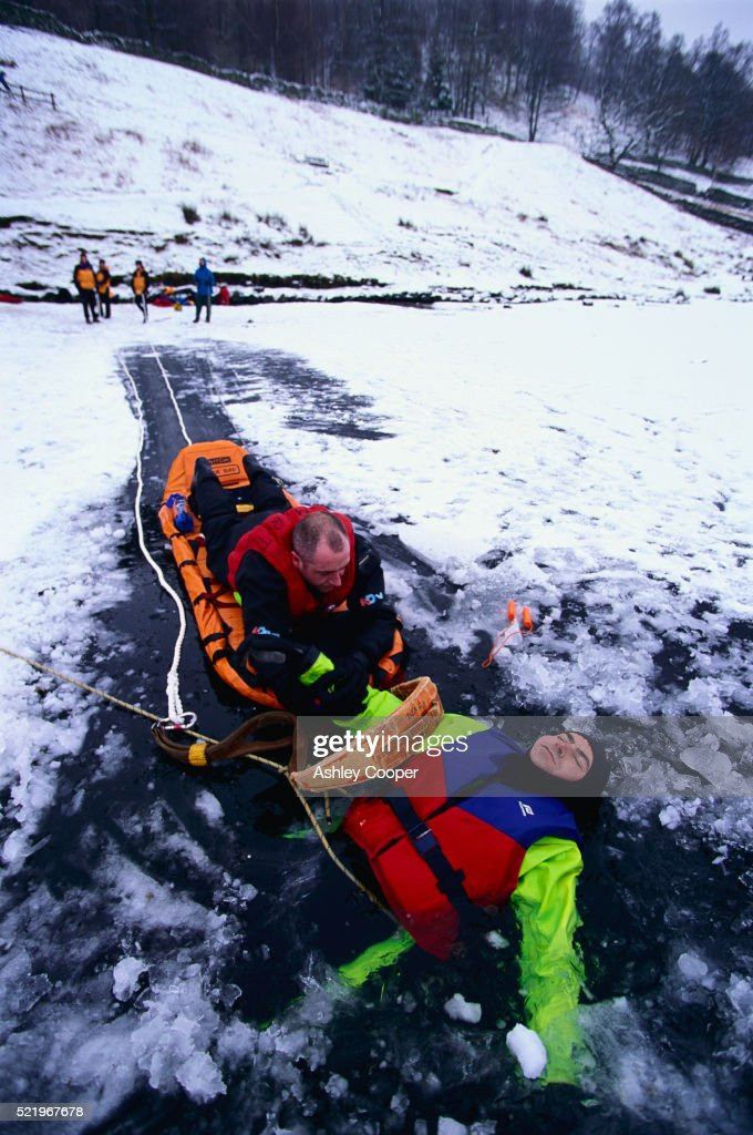 Rescuer Retrieving Man in Frozen Water