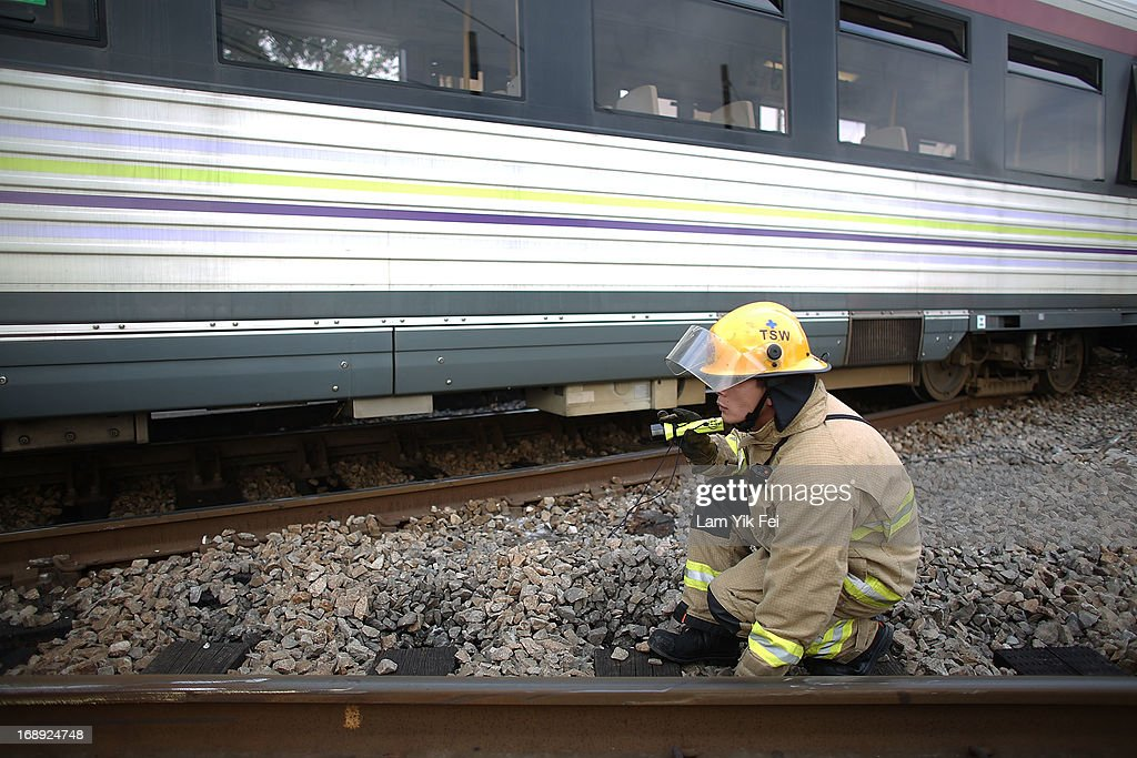 A rescuer searchs for any people trap at the scene after the crash of two light railway trains on 17 May, 2013, near Hang Mei Tsuen Station at Tin Shui Wai in Hong Kong. Over 62 people are hurt in the accident, in which three victims are seriously injured. on May 17, 2013 in Hong Kong, Hong Kong.