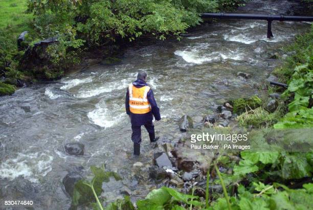 A rescuer trawls the Stainforth Beck to search for two school girls who were swept away as they walked through the fast flowing river during a school...