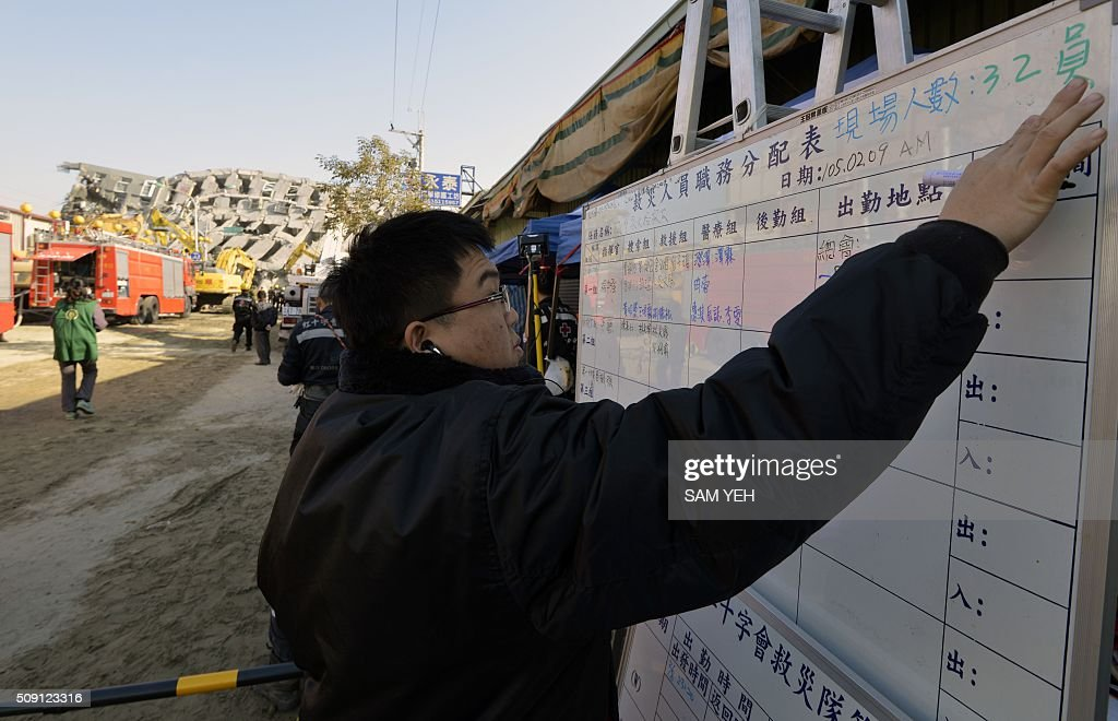 A rescuer updates the information notice board in front of the collapsed Wei-Kuan complex in Tainan, southern Taiwan, on February 9, 2016. Rescuers deployed heavy machinery in a renewed effort to locate more than 100 people trapped in the rubble of a Taiwan apartment complex felled by an earthquake as the 72-hour 'golden window' for finding survivors passed. AFP PHOTO / Sam Yeh / AFP / SAM YEH