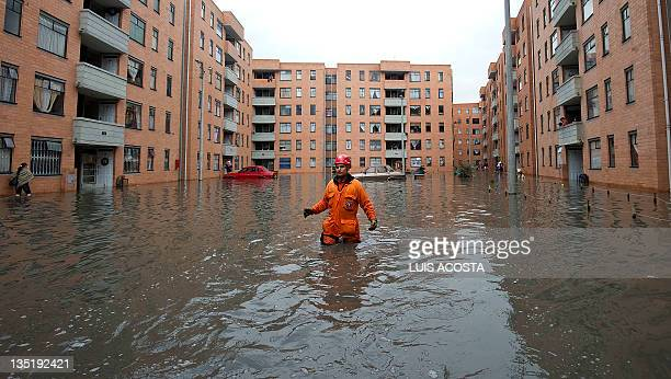 A rescuer wades through a flooded street next to a residential complex in the Bella Vista neighborhood following the overflowing of the Bogota River...