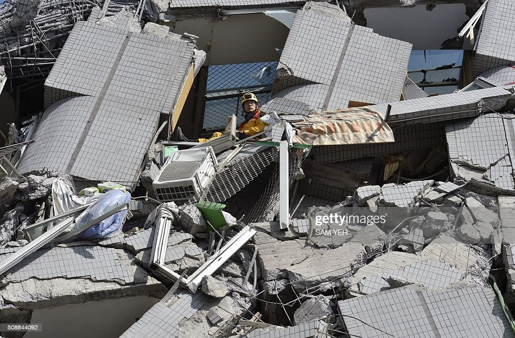 A rescuer waits for a crane at the collapsed Wei Kuan complex building on the second day of rescue operations following a 6.4 magnitude earthquake in southern Taiwan's city of Tainan on February 7, 2016. Rescuers raced against time February 7 to free more than 100 people buried beneath the rubble of apartment blocks felled by an earthquake in southern Taiwan that left 19 dead, as an investigation was launched into the building collapse. AFP PHOTO / Sam Yeh / AFP / SAM YEH