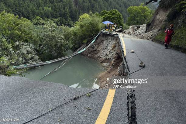 A rescuer walks past a damaged section of road in Jiuzhaigou two days after a 65magnitude earthquake hit southwest China's Sichuan province on August...