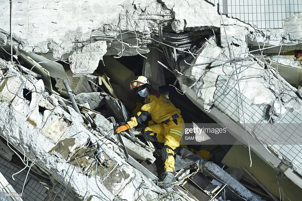 A rescuer works at the site of a collapsed building in the southern Taiwanese city of Tainan on February 6, 2016 following a strong 6.4-magnitude earthquake. A powerful earthquake in Taiwan felled a 16-storey apartment complex full of families who had gathered for Lunar New Year celebrations in the early hours of February 6, with at least seven dead and more than 30 feared trapped. AFP PHOTO / Sam Yeh / AFP / SAM YEH