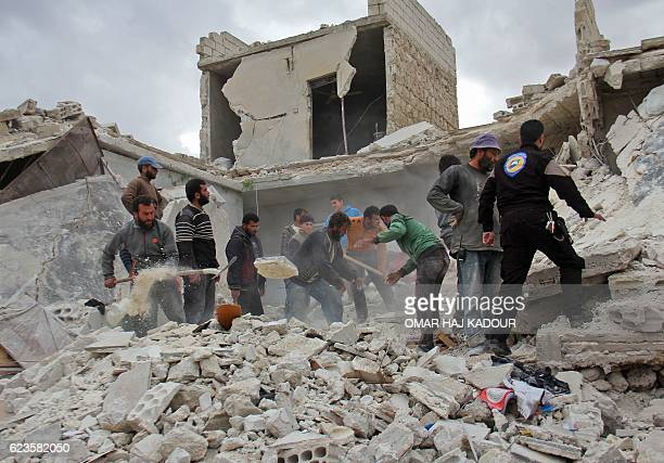 TOPSHOT Rescuers and civilians inspect a destroyed building in the Syrian village of Kfar Jales on the outskirts of Idlib following air strikes by...