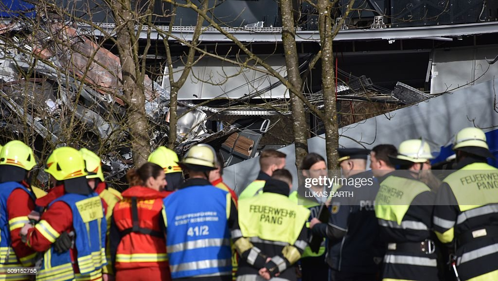 Rescuers and emergency doctors gather at the site of a train accident near Bad Aibling, southern Germany, on February 9, 2016. Two commuter trains collided head-on near Bad Aibling, around 60 kilometres (40 miles) southeast of Munich, killing at least nine people and injuring around 100, in what is believed to be the country's first deadly rail accident in three years. / AFP / LUKAS BARTH