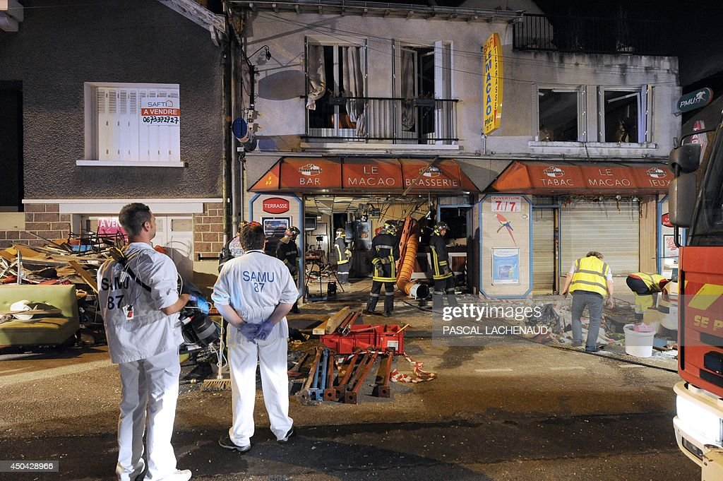Rescuers and firefighters at work following an explosion at the bar 'Macao' in downtown Limoges, central France, early on June 11, 2014. A resident, believed to be drunk and having a dispute with his wife, took refuge in the cellar of the family home and opened the gas, causing a huge explosion which seriously injured him.