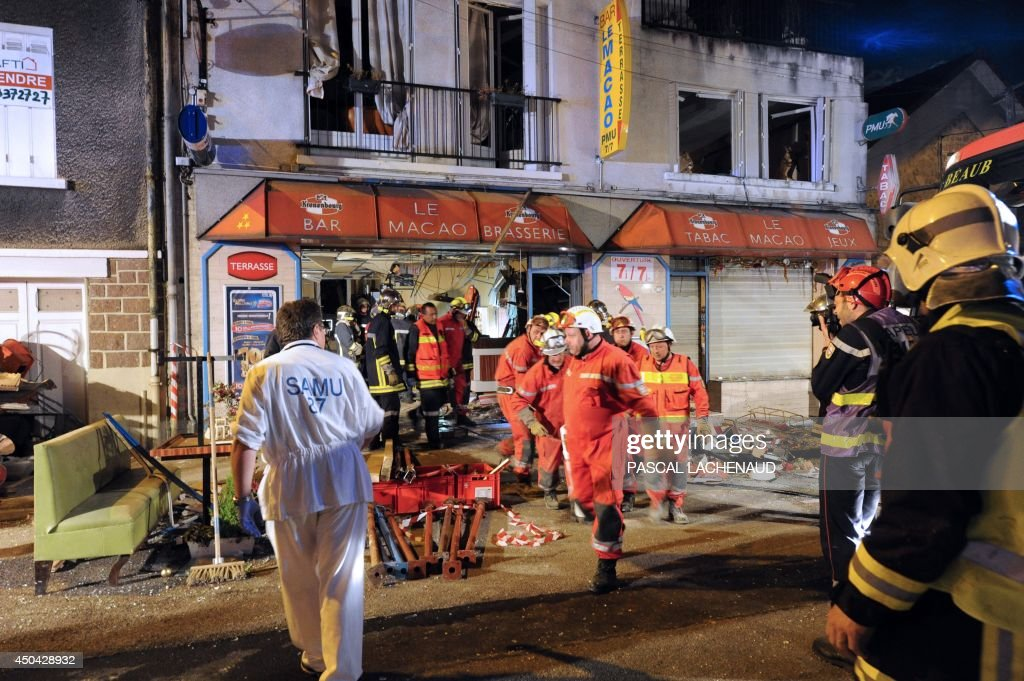 Rescuers and firefighters evacuate an injured man following an explosion in front of the bar 'Macao' in downtown Limoges, central France, early on June 11, 2014. A resident, believed to be drunk and having a dispute with his wife, took refuge in the cellar of the family home and opened the gas, causing a huge explosion which seriously injured him.