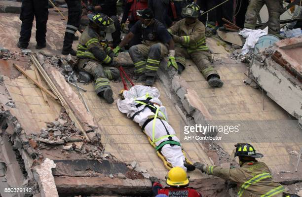 TOPSHOT Rescuers and firefighters lower the corpse from a house that was destroyed after a powerful quake in Mexico City on September 20 2017 A...